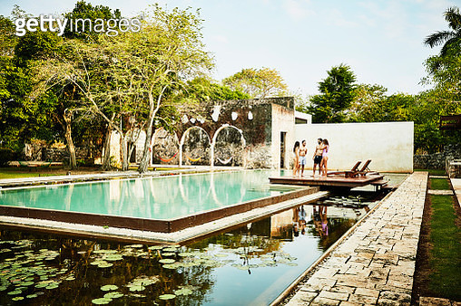 Two couples relaxing by edge of pool at luxury tropical resort - gettyimageskorea