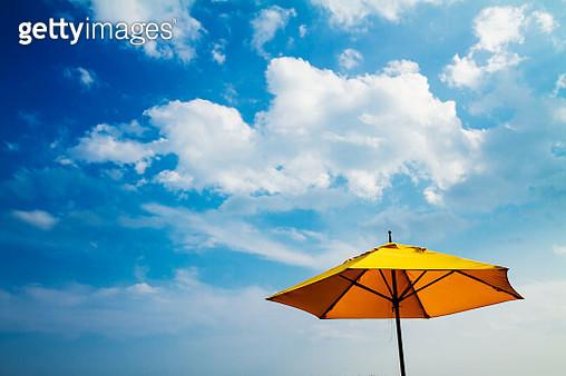 Yellow umbrella and sunny sky - gettyimageskorea