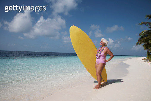 Senior woman carrying surfboard on beach, smiling, side view - gettyimageskorea