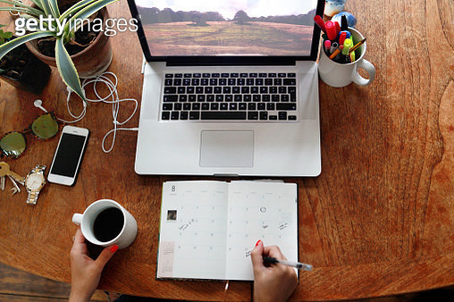 Person writing in diary with laptop on desk - gettyimageskorea