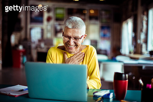 Close up of a senior woman working in a office - gettyimageskorea
