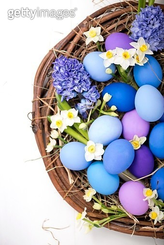 Blue and purple Easter eggs with spring flowers in a wicker basket - gettyimageskorea