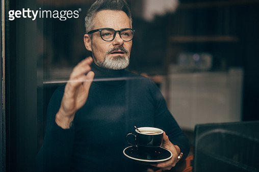 Mature man sitting in the coffee shop and looking through window - gettyimageskorea