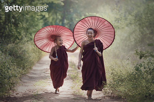 Two young monks with umbrellas laughing. - gettyimageskorea