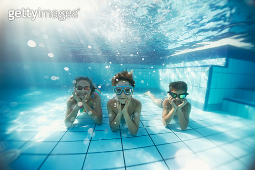 Happy kids enjoying summer vacations in the swimming pool. Kids are lying on the bottom at smiling at the camera.Shot with Nikon D850. - gettyimageskorea