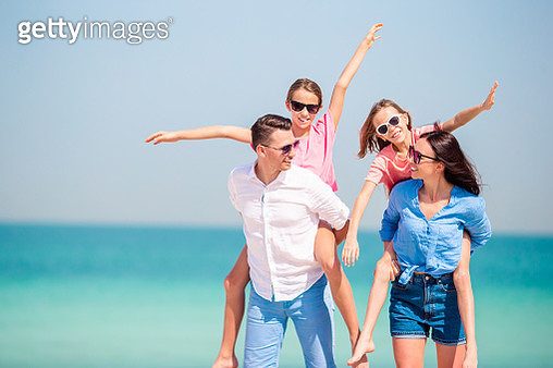 Happy Parents Piggybacking Daughters Against Sea - gettyimageskorea