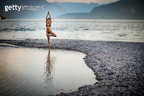 Woman making yoga by the lake. - gettyimageskorea