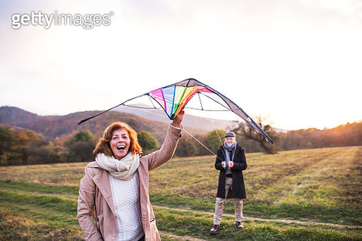 Carefree Senior Couple Flying A Kite In An Autumn Nature At Sunset. - gettyimageskorea
