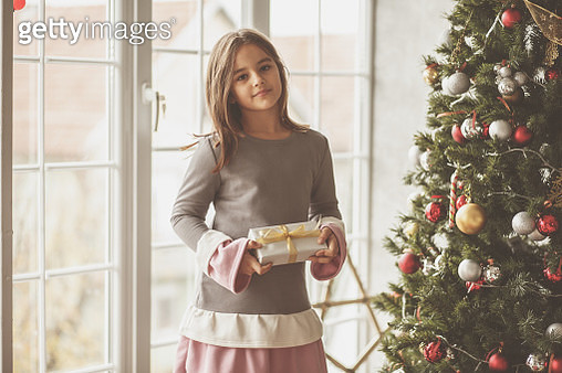 Shot of cute little girl standing next to a Christmas tree in her living room and holding a Christmas gift while smiling and looking at camera. - gettyimageskorea