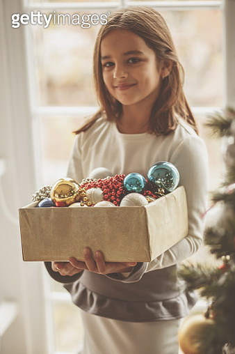 Selective focus of cute little girl holding a box of Christmas bobbles and ornaments and standing next to a Christmas tree. She is looking at camera with a smile on her face. - gettyimageskorea