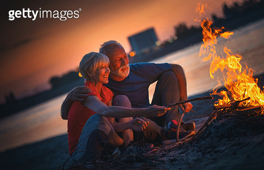 Closeup of late 50's couple having some sitting at a river bank, throwing sticks in a fire and enjoying this beautiful summer evening. - gettyimageskorea