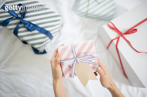 female hand holding gift box with gift tag on the bed - gettyimageskorea