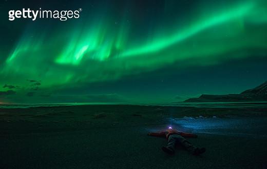 A man lying under a aurora at night. - gettyimageskorea