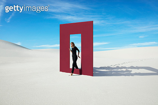 Young fashion model walking through red door frame at desert against sky during sunny day - gettyimageskorea