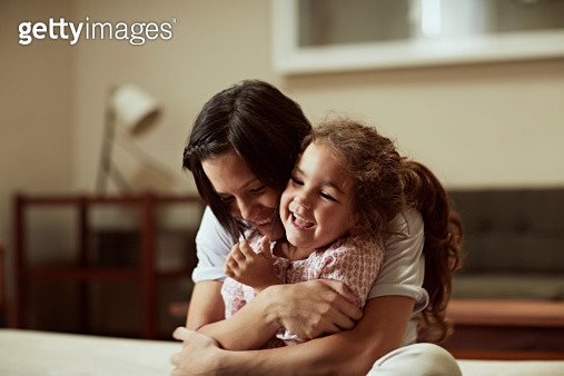 Mother and daughter having fun on sofa - gettyimageskorea