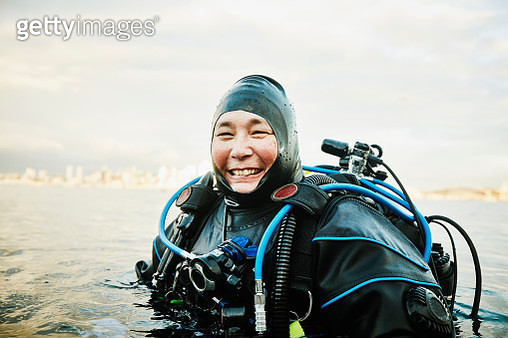Portrait of smiling female diver standing in water before open water dive - gettyimageskorea