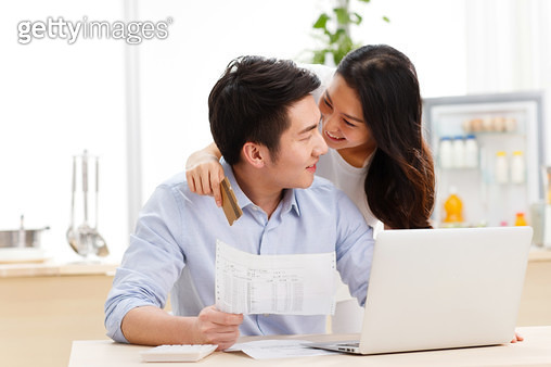 Couple doing computer in kitchen - gettyimageskorea