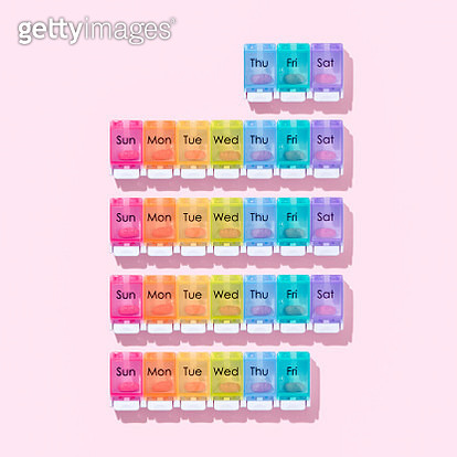 Pill Organizer Arranged by One Calendar Month on Pink Colored Background. - gettyimageskorea