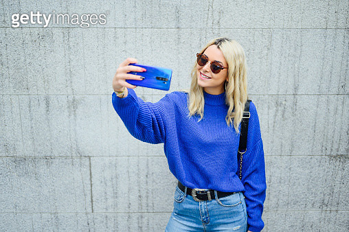 pretty blonde woman with sunglasses taking a selfie with mobile in the city - gettyimageskorea