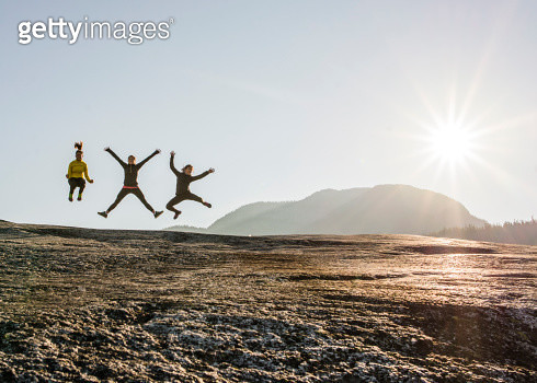 Three young female hikers jumping mid air on rock, Squamish, British Columbia, Canada - gettyimageskorea