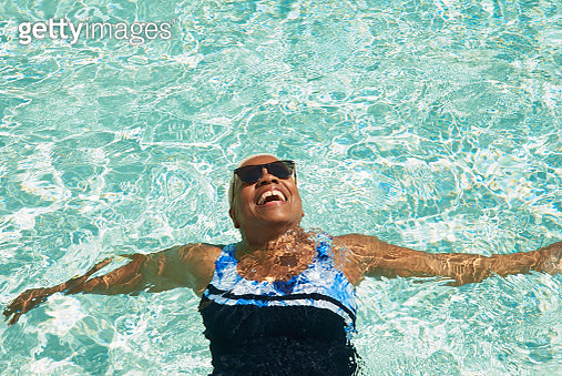 An older woman relaxes on her back in the pool enjoying the sunshine - gettyimageskorea