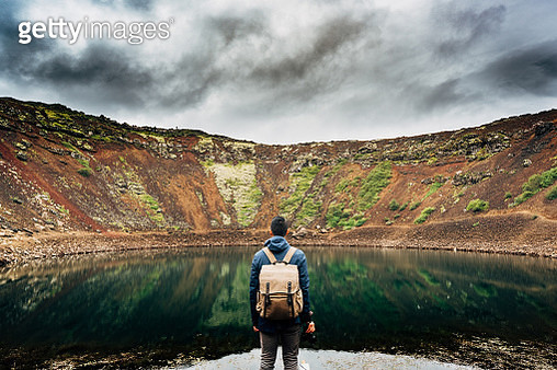 Rear View Of Man Looking At Lake - gettyimageskorea