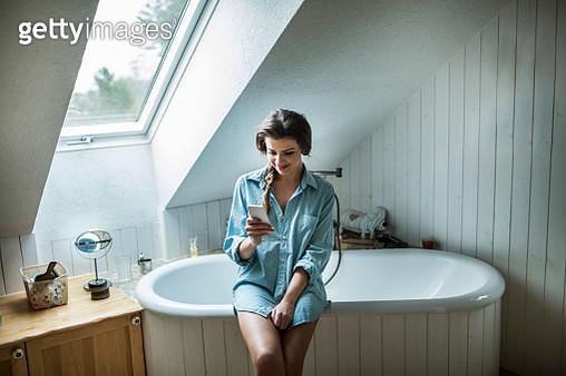 Young woman in bathroom using smartphone - gettyimageskorea