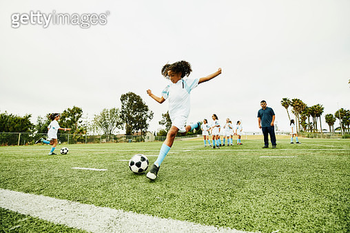 Coach watching young female soccer player practicing shot before game - gettyimageskorea