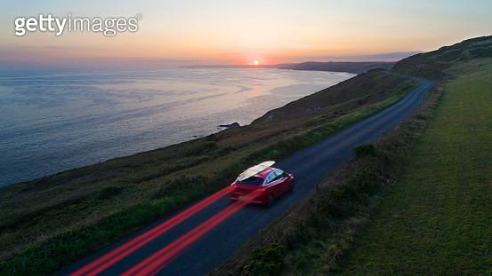 Car driving along coastal road at sunset - gettyimageskorea