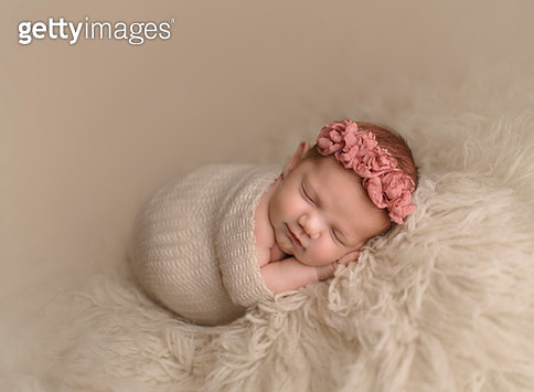 Cute sleeping baby girl wrapped in blanket on rug at home - gettyimageskorea