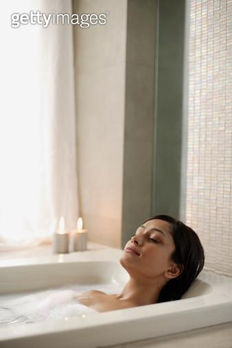 Woman reclining in bathtub - gettyimageskorea