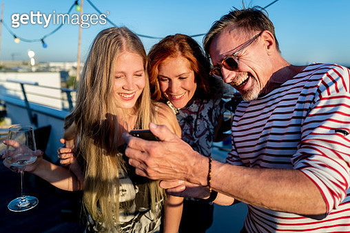 group of friends looking at smartphone on a urban rooftop - gettyimageskorea
