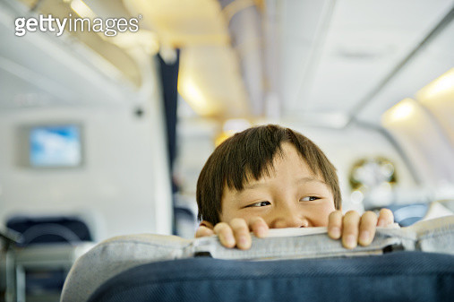 Boy looking over business class seat of plane - gettyimageskorea