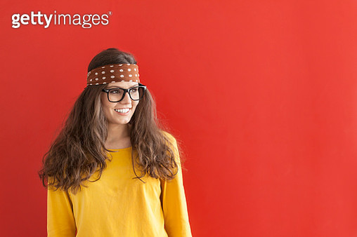 Smiling hippie woman on red background - gettyimageskorea