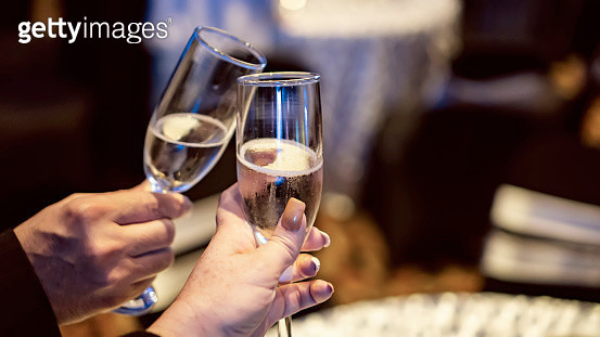 Close up of couple cropped hands making a toast during event celebration - gettyimageskorea