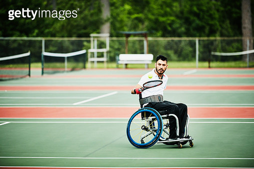 Adaptive athlete warming up for wheelchair tennis match - gettyimageskorea