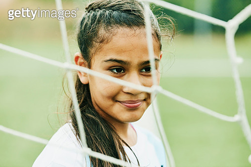 Portrait of smiling young female soccer player standing in front of goal - gettyimageskorea