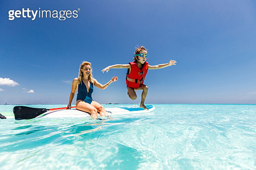 Playful little boy having fun while jumping from a paddle board while his mother is on it. Copy space. - gettyimageskorea