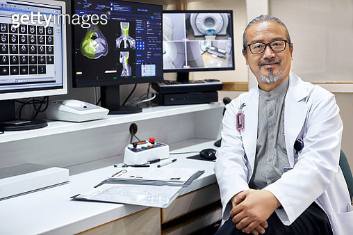 Portrait of confident mature doctor sitting by desk. Male healthcare worker is wearing lab coat. He is working at hospital. - gettyimageskorea