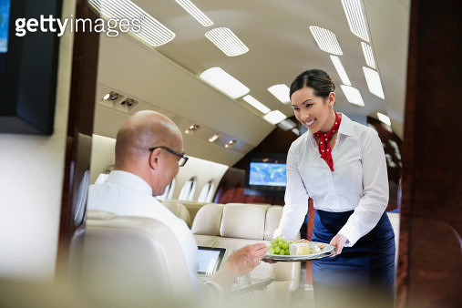 Flight attendant serving food to male passenger in airplane - gettyimageskorea