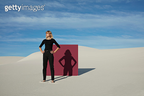 Confident young woman with hands on hip standing against maroon portal at desert during sunny day - gettyimageskorea