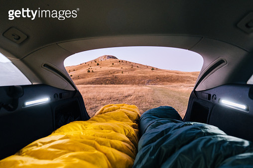 POV down two sleeping bags camping in the back of a car to distant hills - gettyimageskorea