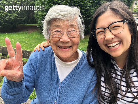 Happy Chinese grandma in her 90s making peace sign with granddaughter in her 20s outside in park. - gettyimageskorea