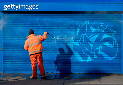 Washing graffiti off a security grill. - gettyimageskorea