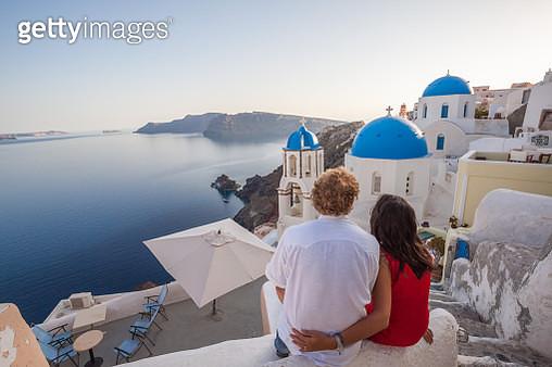 Couple of tourists looking at sunset, Santorini - gettyimageskorea