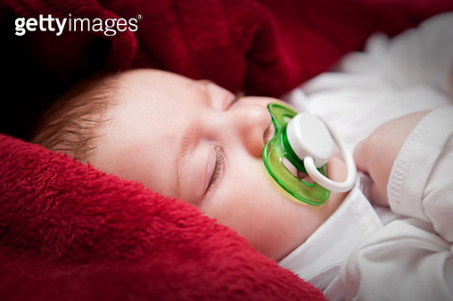 Lovely 3 months baby sleeping on bed covered with red blanket - gettyimageskorea