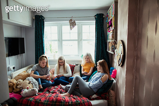 A small group of teenage girls on their phones, lying down in a bedroom. - gettyimageskorea