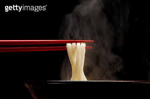 Japanese Udon noodle lifted up by red chopsticks with steam against black background - gettyimageskorea