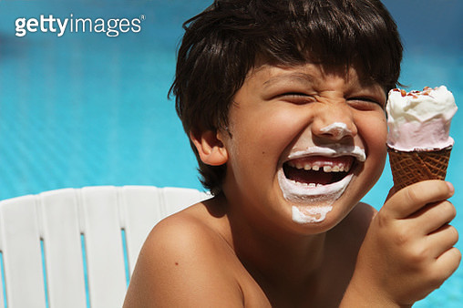 Boy (7-9) eating ice cream by swimming pool - gettyimageskorea