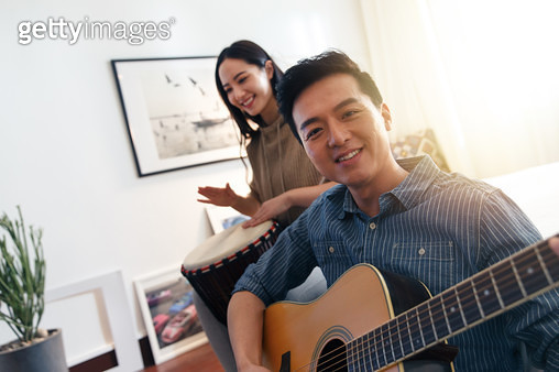 Happy couples playing Musical Instruments at home - gettyimageskorea